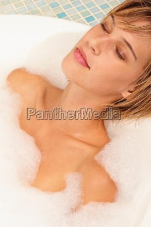 young woman relaxing in bubble bath