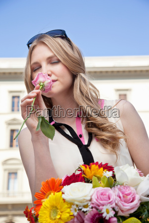 mujer joven oliendo rosa de ramo