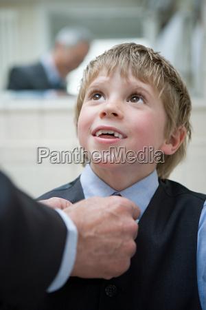 boy having his tie adjusted