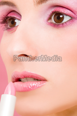 woman applying pink lipstick