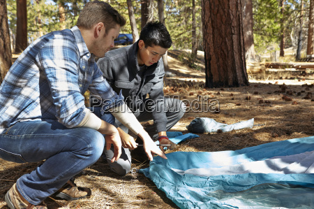 two young men preparing to camp