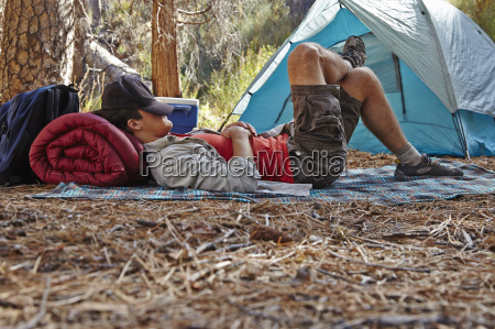 young male camper resting in forest