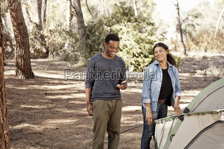 young couple preparing tent to camp