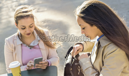 young adult female twins reading smartphone