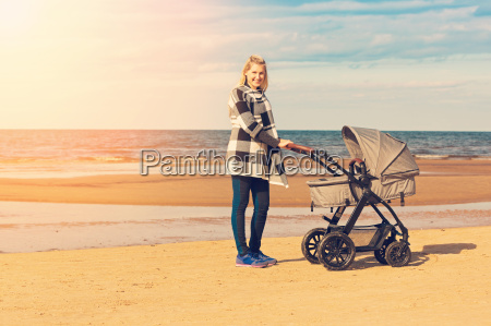 smiling young mother with baby carriage