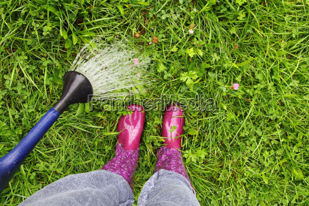 a woman wearing rubber boots pours