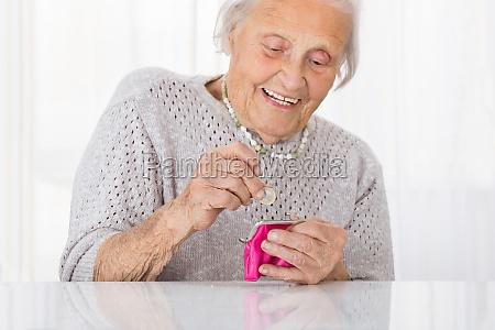 mujer senior inserting coin in monedero