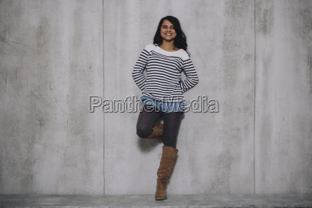 indio hembra apoyada en muro de
