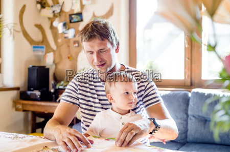 father and son reading book at