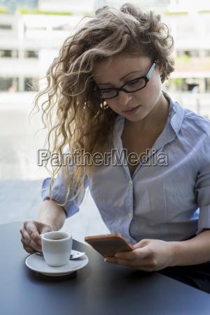 businesswoman revisando el telefono celular en