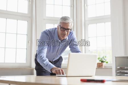 mature businessman using laptop at office