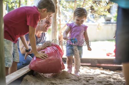 family filling sand into sandpit