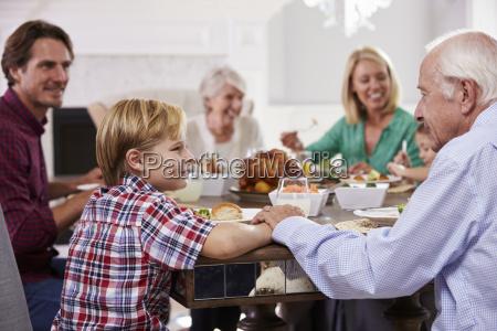 familia extendida sit around table comer