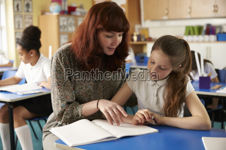 teacher helps a girl at her