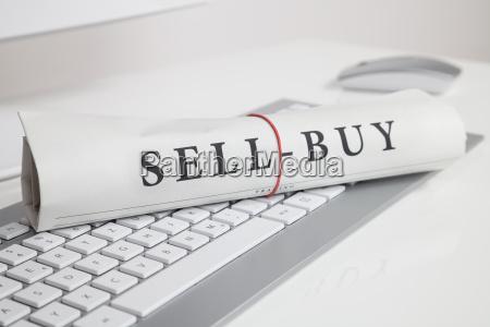 sell buy written on newspaper