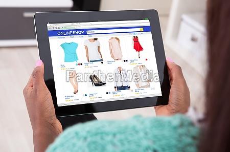 mujer sosteniendo tableta digital en casa