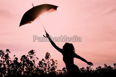 mujer desconectada en silueta con paraguas