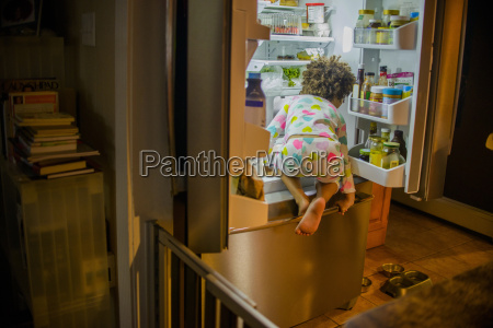 rear view of girl sneaking food