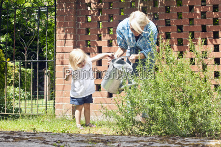female toddler helping mother with watering