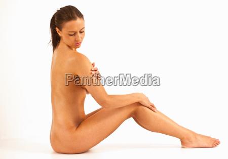 nude woman examining shoulder