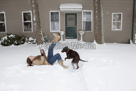 mid adult woman lying in snow