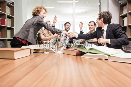 lawyers shaking hands in meeting