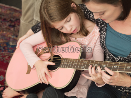 mid adult woman teaching daughter to