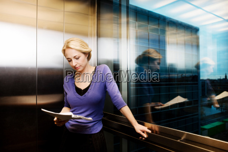 woman in elevator reading a
