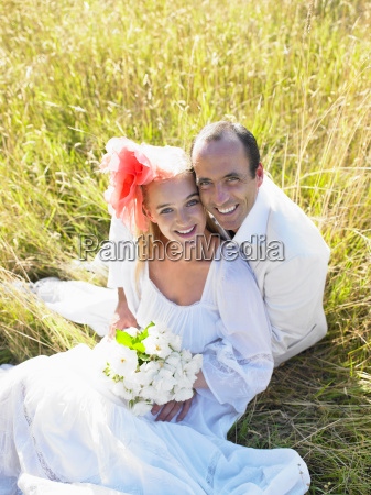married couple sitting in a field