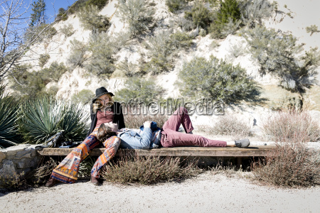 young couple relaxing on bench chilao