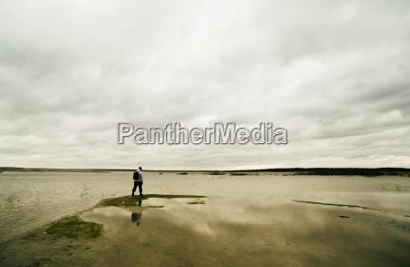 young man hiking beside lake