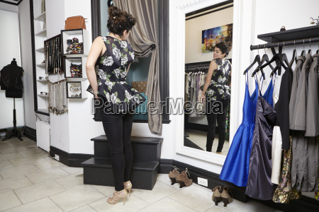 mature woman in fashion boutique looking