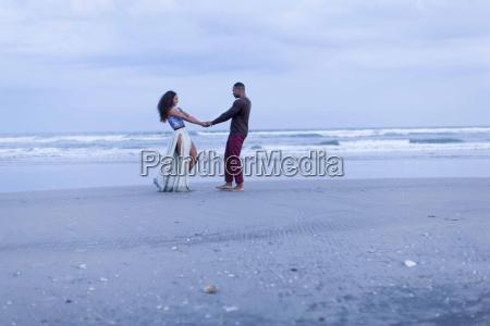 couple fooling around on beach holding