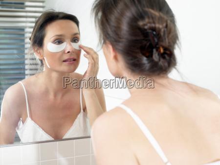 mujer, en, el, baño, aplicando, una, mascarilla - 19502596