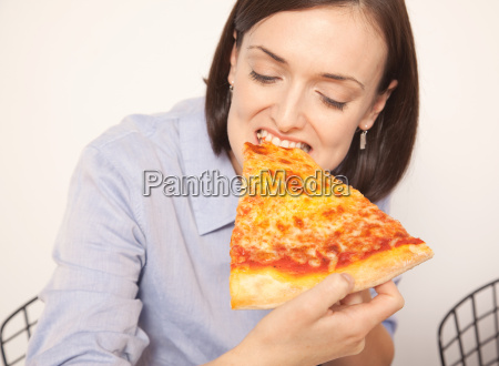 mid adult woman enjoying pizza slice