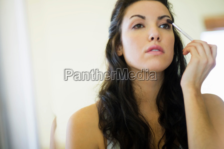 woman applying make up with small