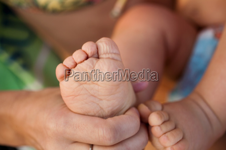 mother touching childs foot close up