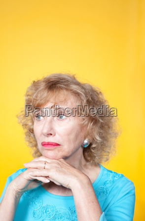 senior woman looking away with hands