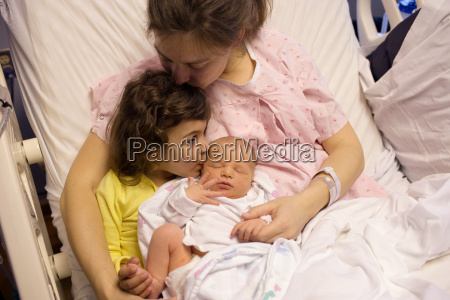 mother holding newborn baby with daughter