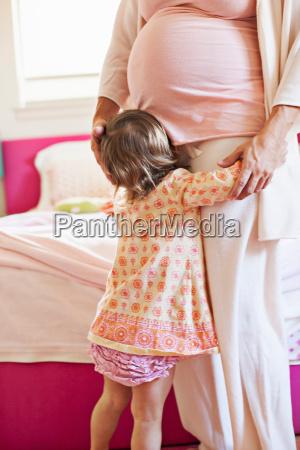 toddler girl hugging pregnant mother