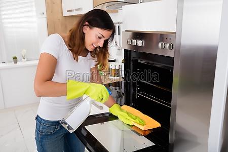 mujer limpiando el horno en la
