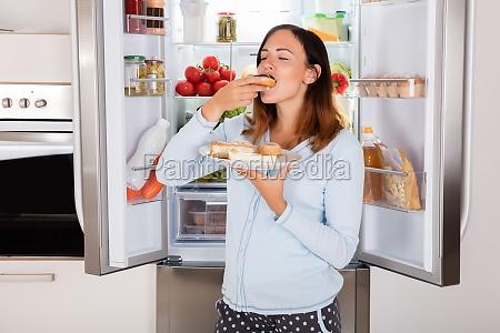 mujer comiendo comida dulce cerca de