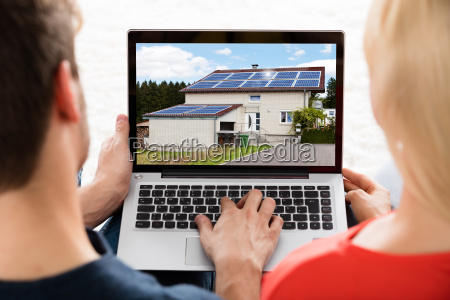 couple looking at house on laptop