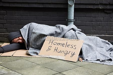 hombre sin hogar y hambriento durmiendo