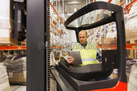 hombre con tablet pc operando carretilla