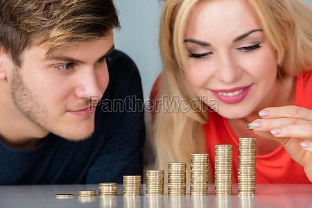 pareja sentada con montones de monedas