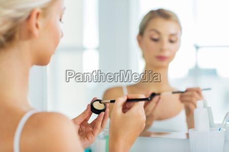 mujer con pincel de maquillaje y