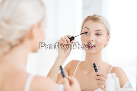 mujer con rimel aplicando maquillaje en