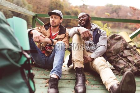 hombres jovenes con mochilas sentados en