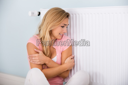 woman, feeling, cold, sitting, near, thermostat - 20118775